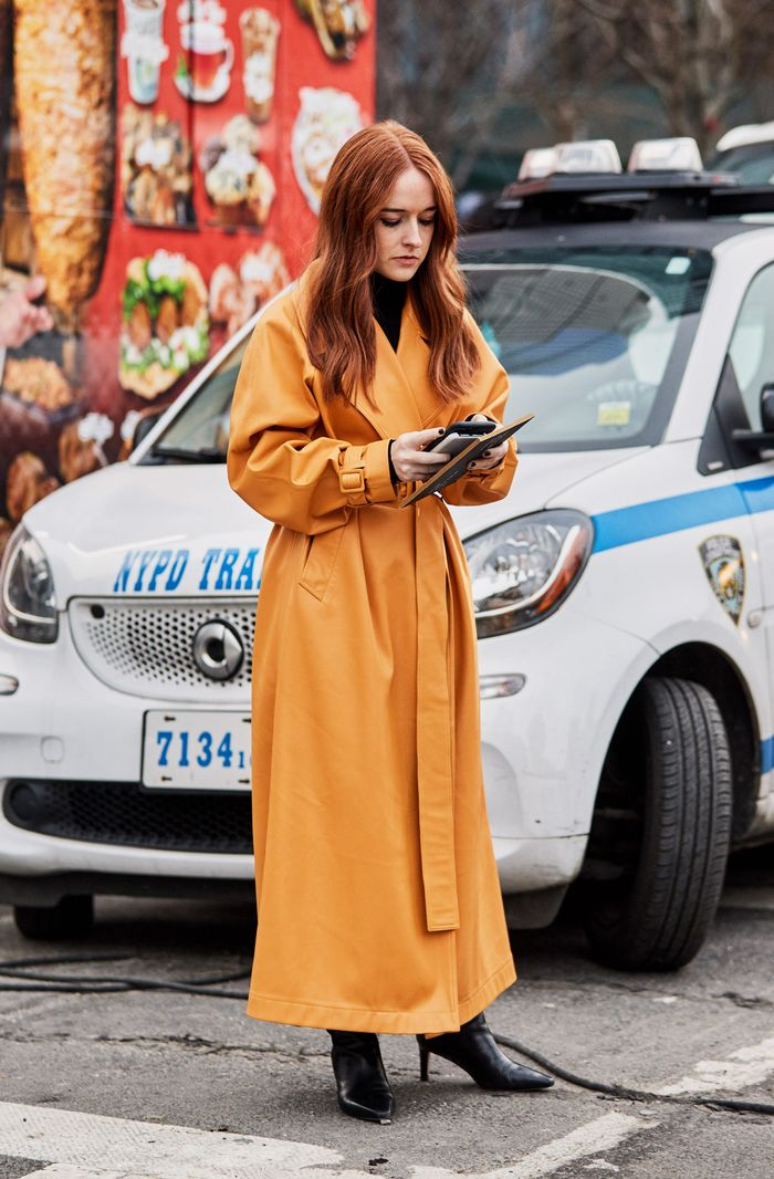 How to wear a trench coat when it is cold: orange trench coat and black boots