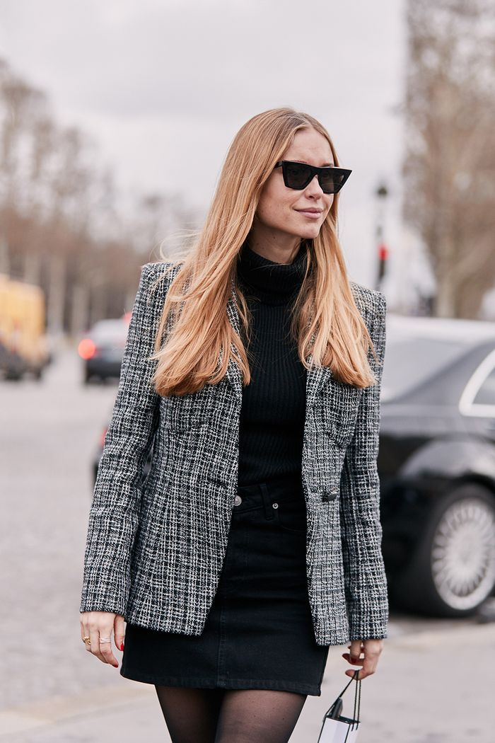 Pernille wearing a tweed blazer and black miniskirt
