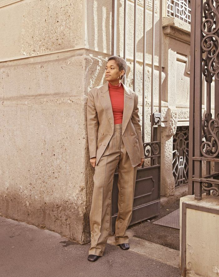 Work outfits: a beige trouser suit with a red roll neck