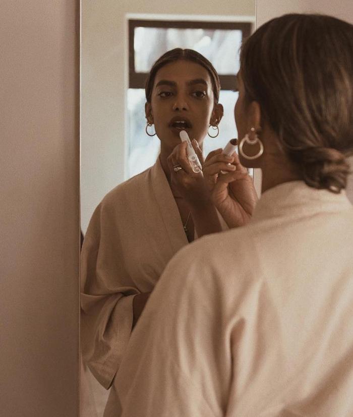 Skincare Fridge Storage: Stella Simona applying lipstick in mirror