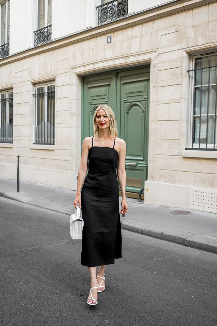 French holiday packing tips from Marissa Cox of Rue Rodier: wearing a black dress, white sandals and bag