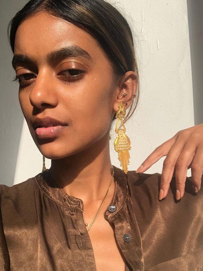 Best Facial Cleansers: Stella Simona wearing brown shirt and gold earrings