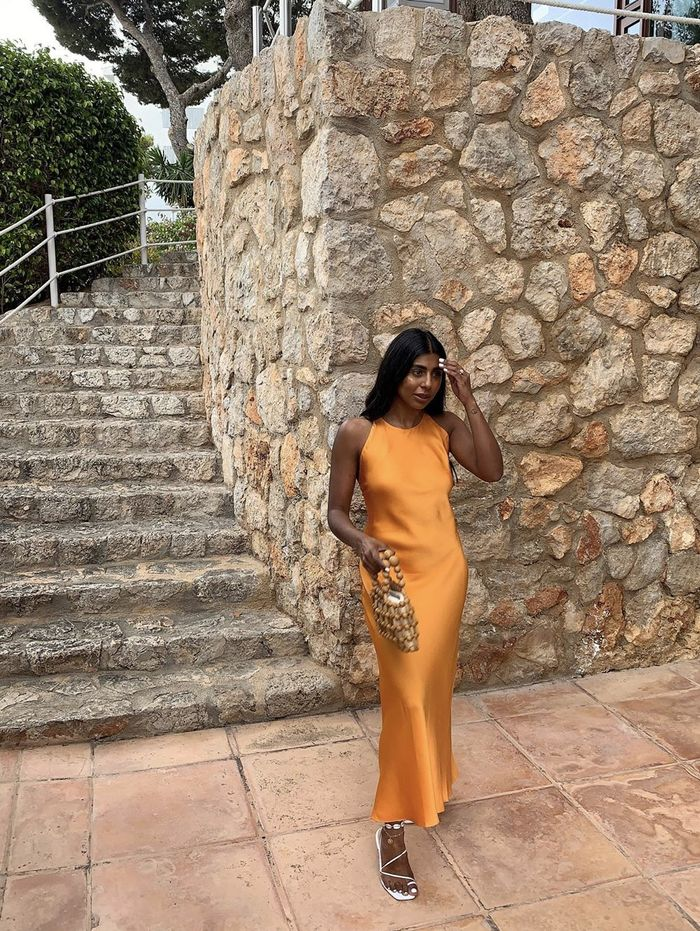 Summer holiday outfits: Monikh in an orange slip dress and white sandals