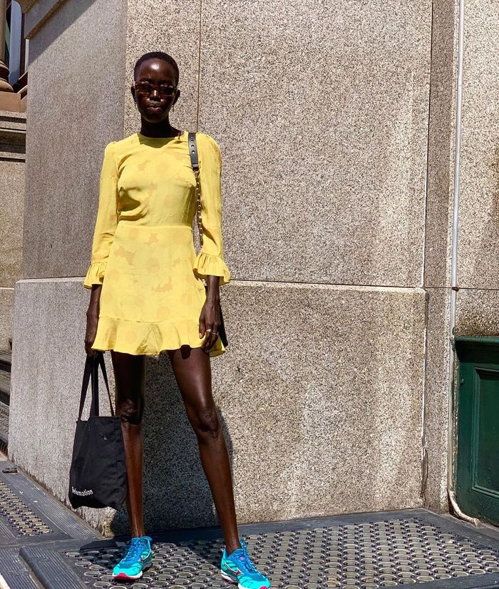 Glycolic acid: Kuoth wearing yellow mini dress and trainers