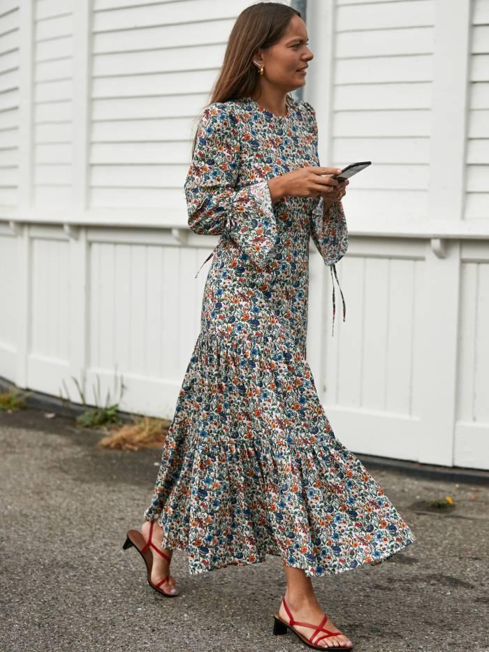 new wedding guest dress brands: woman wearing floral dress during copenhagen fashion week
