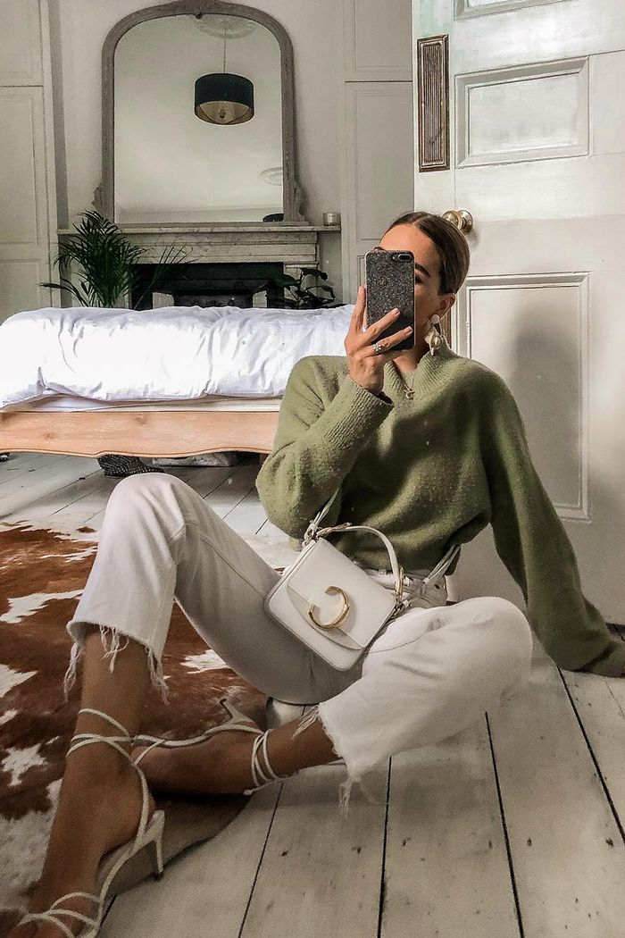 Jessica Skye wearing a green & Other Stories jumper with white jeans and sandals