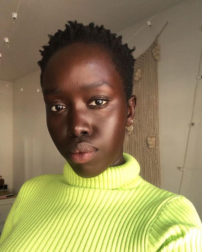 Best foundation alternatives: Kuoth wearing lime jumper and glowy skin