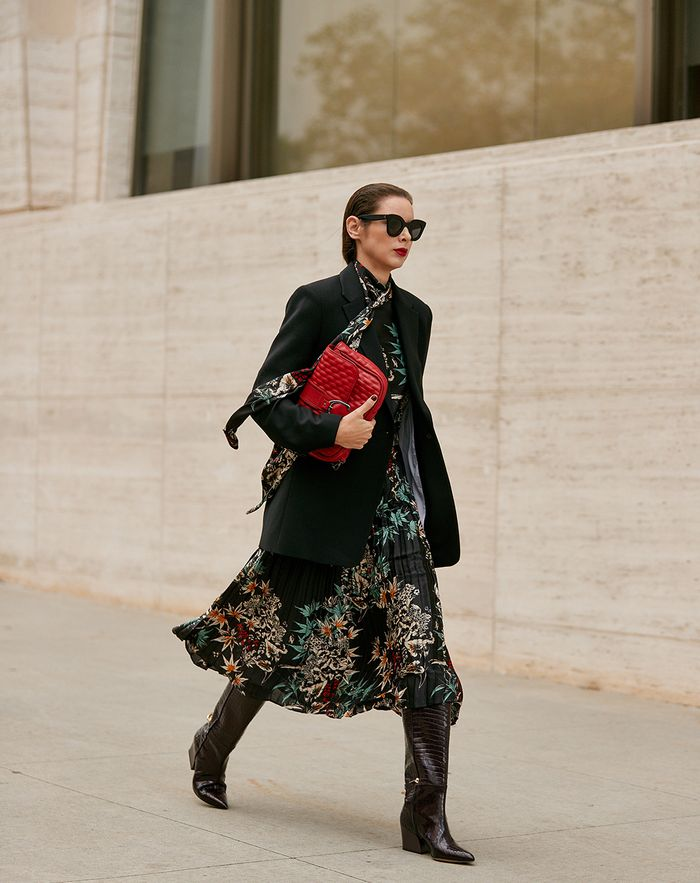 Knee high boot trend 2019: black mock croc boots worn with a floral dress