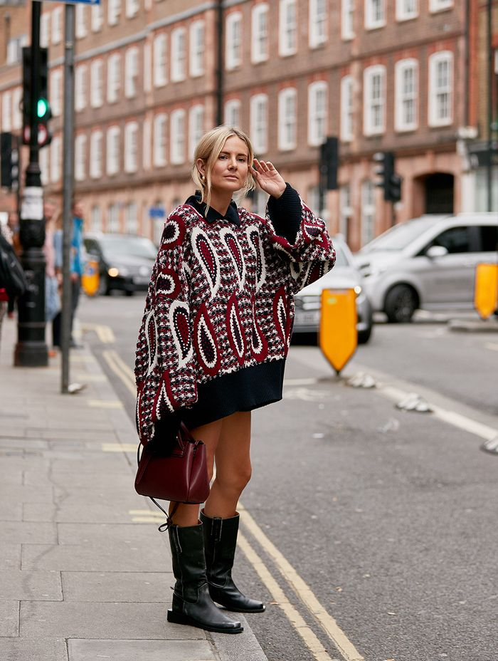 dresses with boots in London: Lucy Williams wearing a paisley jumper dress with black knee boots