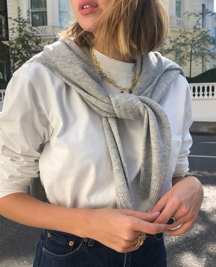 Lizzy Hadfield wearing a grey knotted jumper and white tee