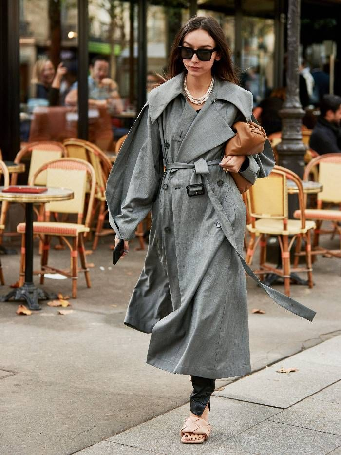 Woman wears grey oversize trench coat paired with Bottega Veneta sandals