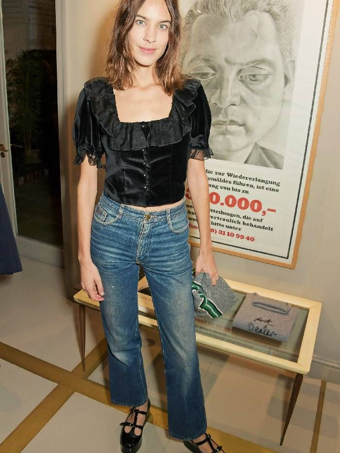 Alexa Chung wears a black velvet top with kick flare jeans and chunky mary-jane shoes