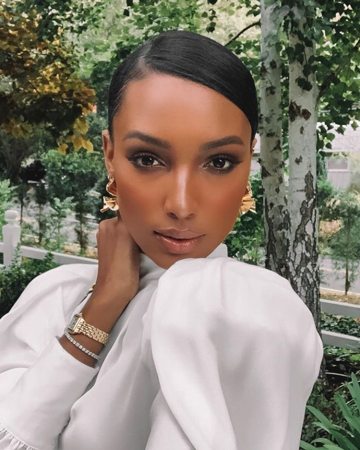 Face Primers for Dry Skin: Jasmine Tookes with slicked-back hair and gold earrings