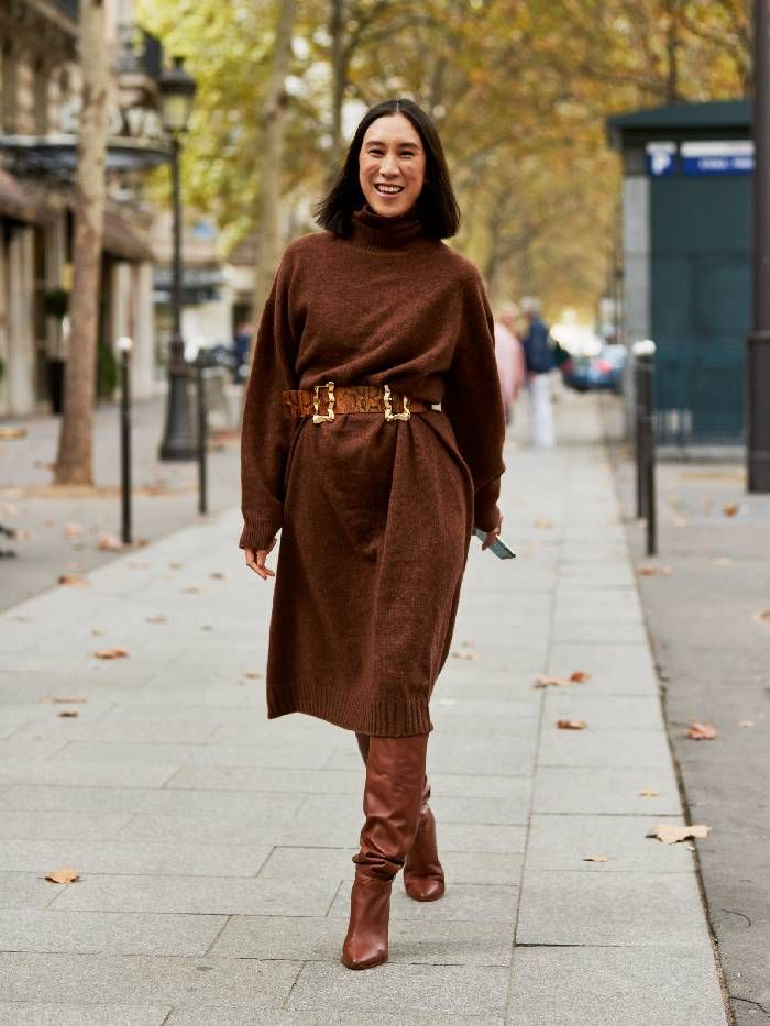 Eva Chen wears brown knitted dress with leather belt and boots.