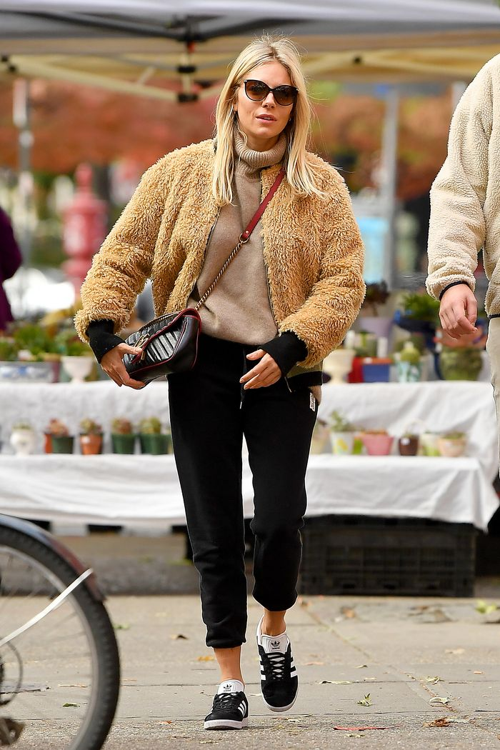 Sienna Miller wears fluffy bomber jacket with beige roll neck knit and black joggers with Adidas Gazelle trainers and Gucci Marmont bag.