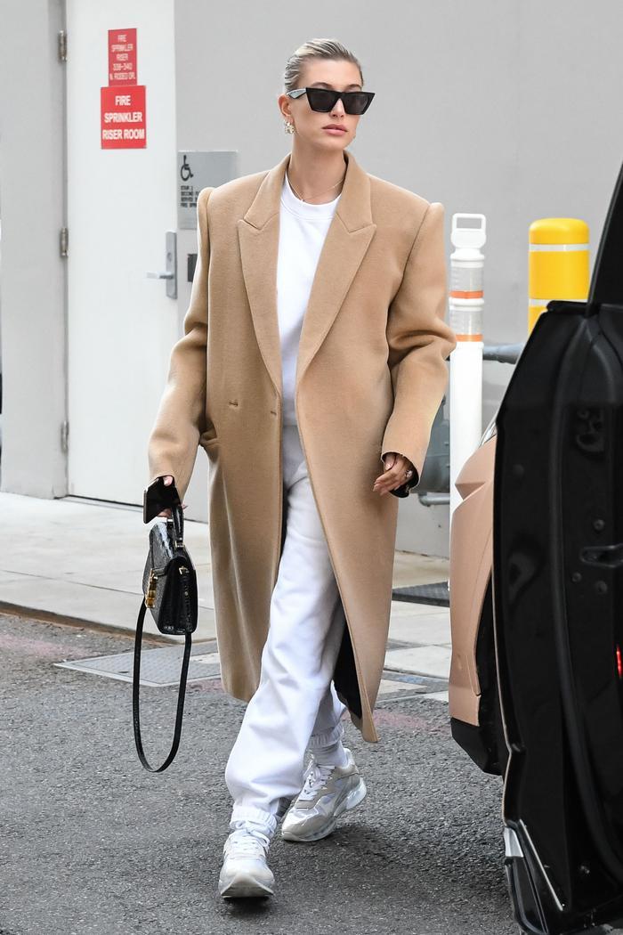 Hailey Bieber Winter Capsule: Hailey Bieber wears a camel coat over a white ensemble