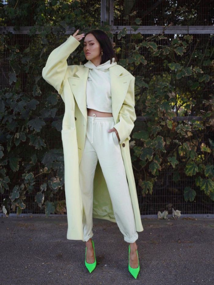 how to wear jogging bottoms: tiffany hsu wearing a matching yellow tracksuit with a yellow coat and green heels