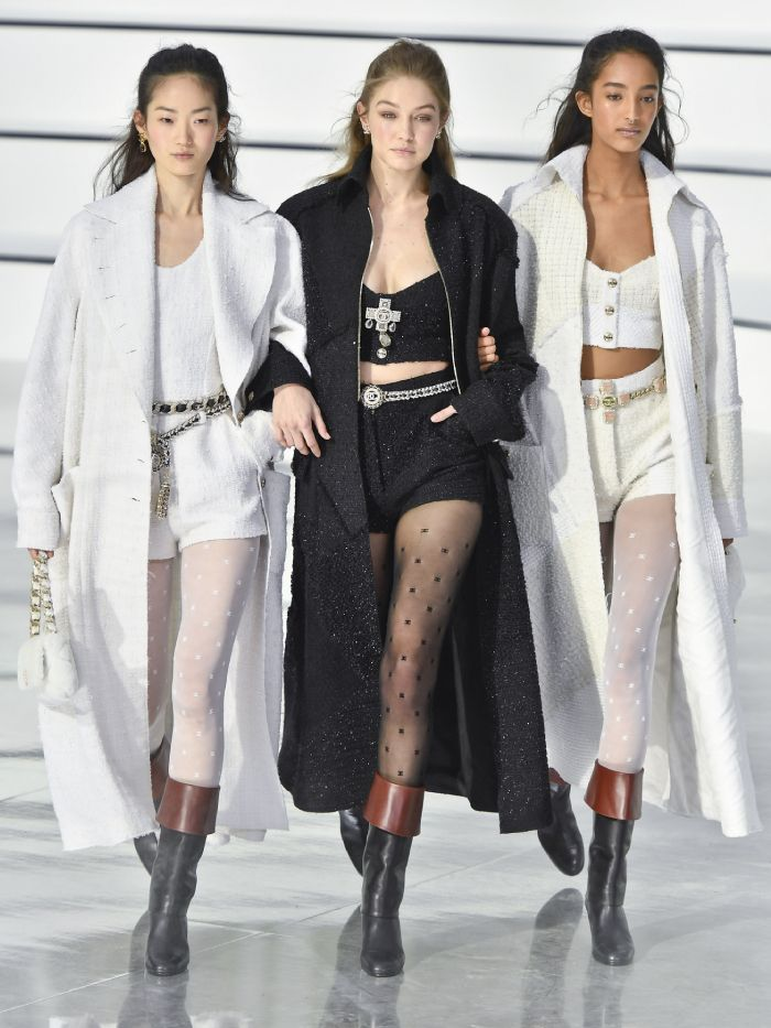 chanel logo tights: models wearing a range of the tights in black and white on the autumn/winter 2020 runway