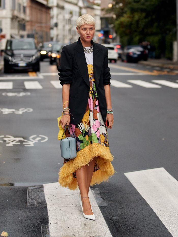 wedding guest outfit trends 2021: a street styler wearing a bold print dress and a black jacket