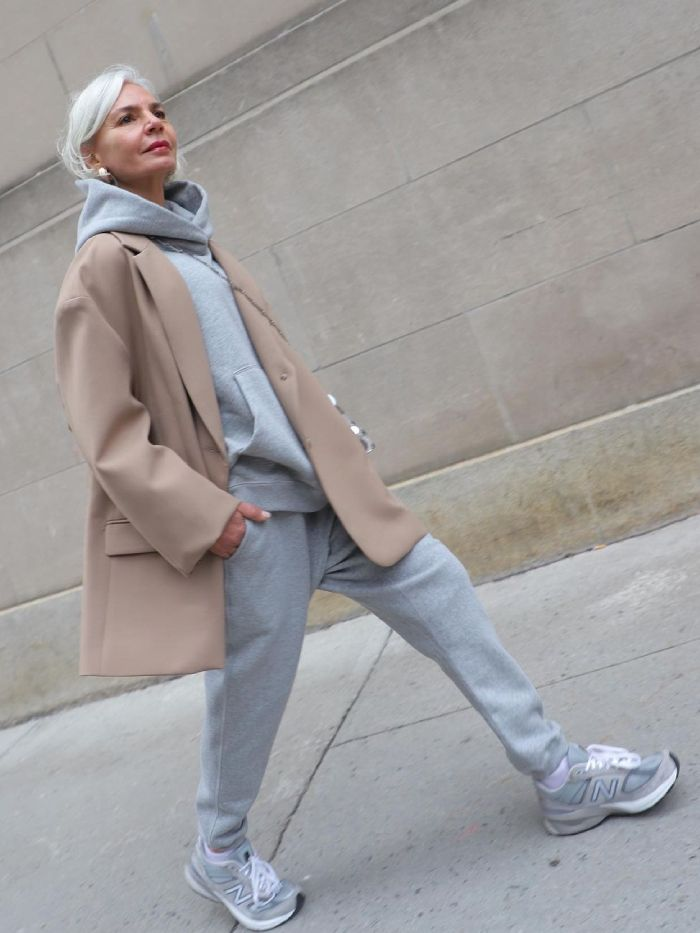 2021 capsule wardrobe: grece ghanem wearing a grey tracksuit with a beige jacket, new balance sneakers and gold earrings and red lipstick