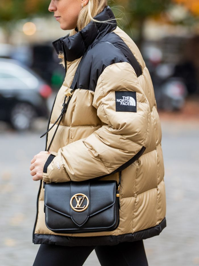 the north face trend: street styler wearing a north face jacket and louis vuitton bag