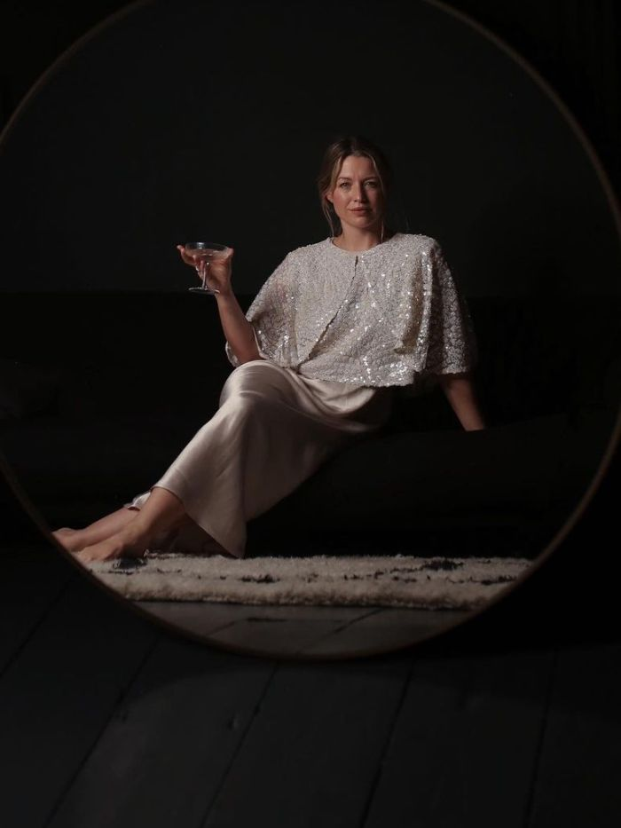 sustainable christmas gift ideas: alexis foreman wearing a sequin top and satin skirt drinking a martini