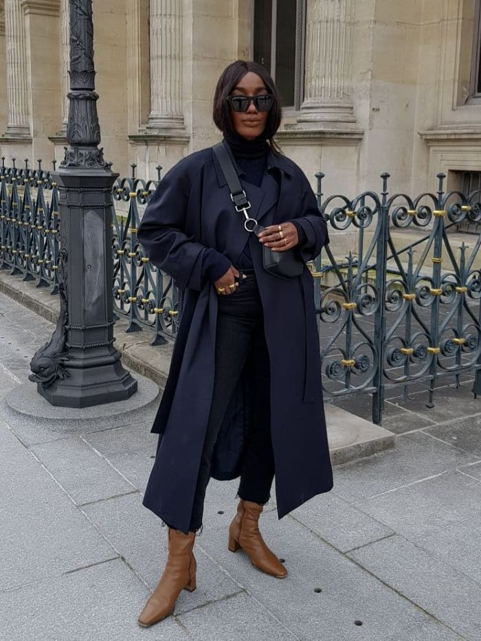 zara sister brands: Aïda of Basics Touch wearing a Berksha bag with a blue trench coat, black jeans and brown boots