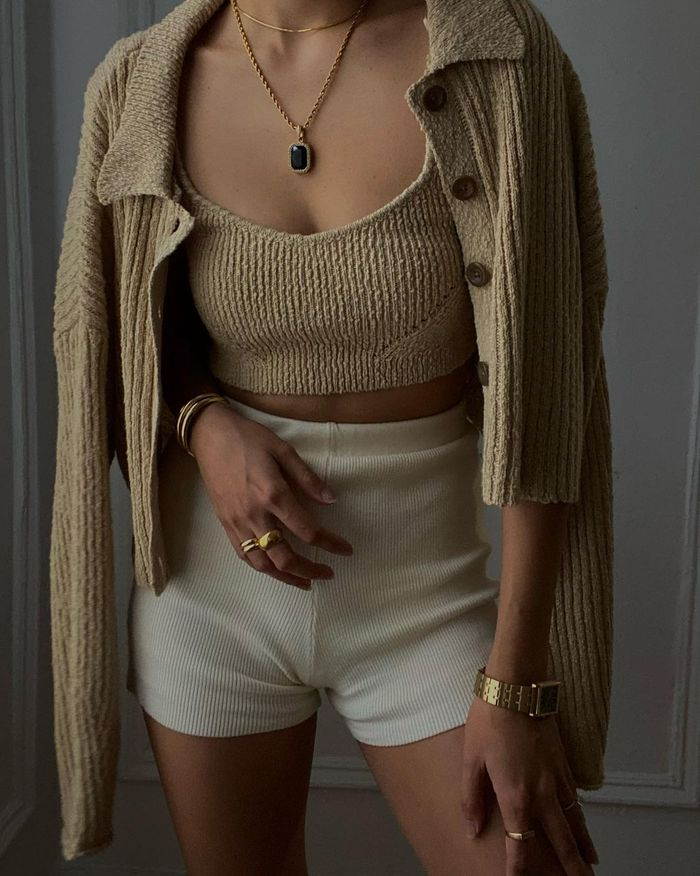 Knitted Shorts Trend: @dawn.tan wears a pair of cream knitted shorts with a camel cardigan