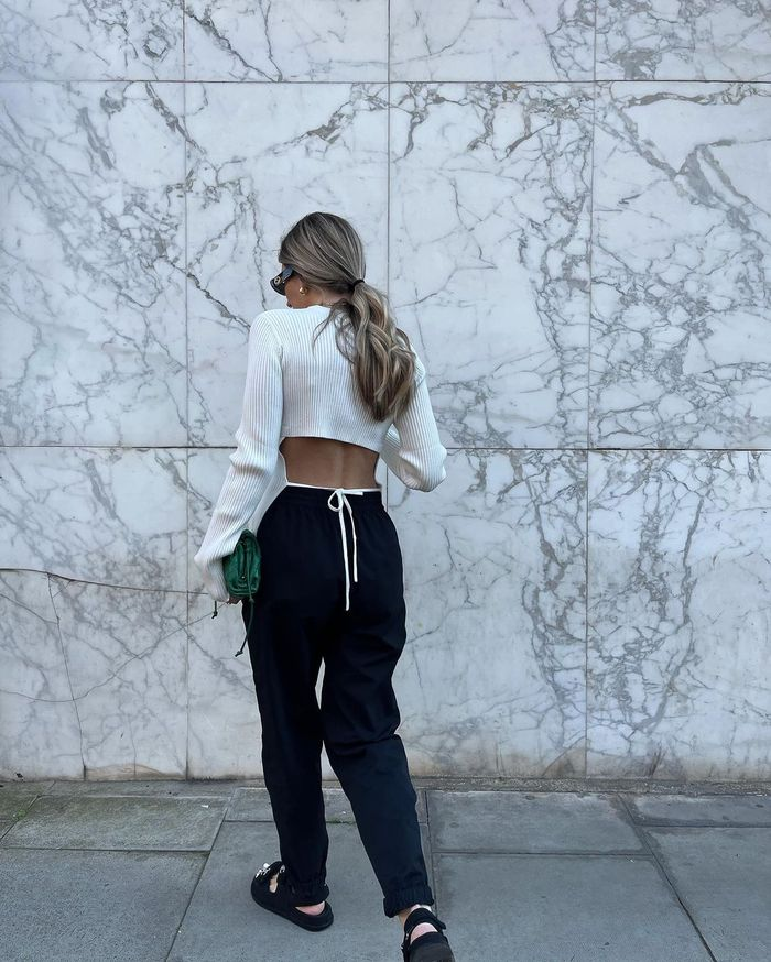 Trouser trends 2021: black trousers and white backless top