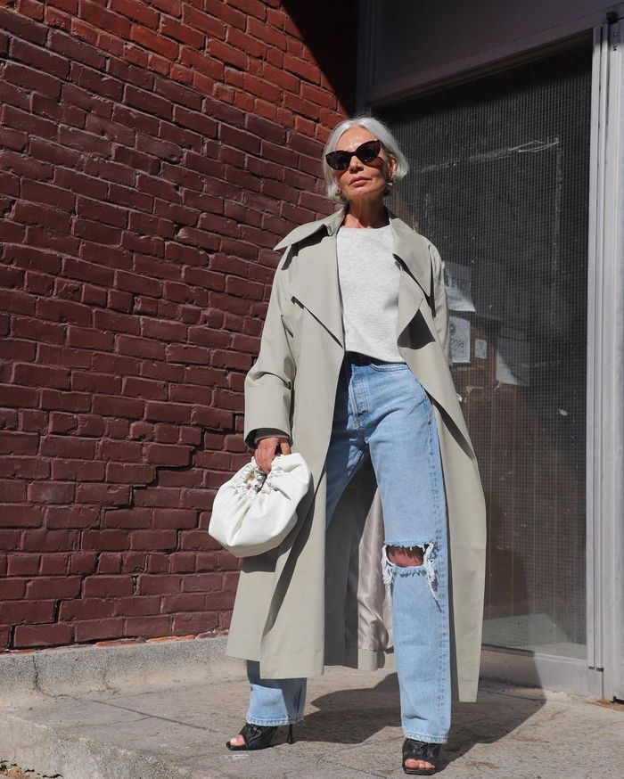 what to wear with a trench coat: Grece Ghanem in a coat with ripped jeans