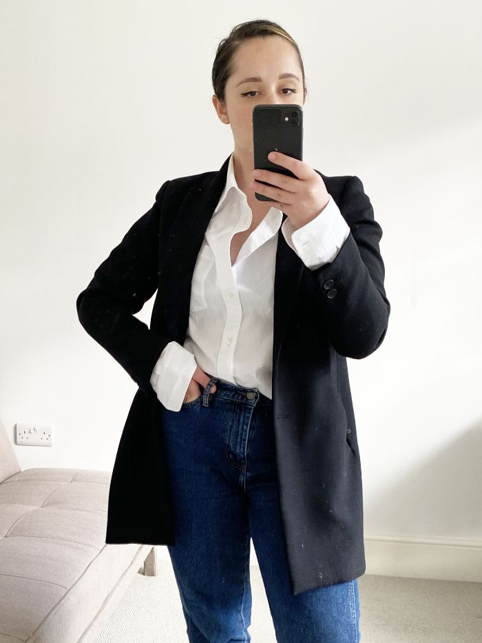 wardrobe staples for women in 30s: elinor block wearing a black jacket, white shirt and blue jeans