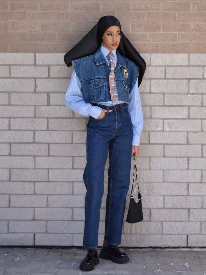 vintage jeans: hodan yousuf wearing blue denim jeans and a cut-out denim jacket and blue shirt