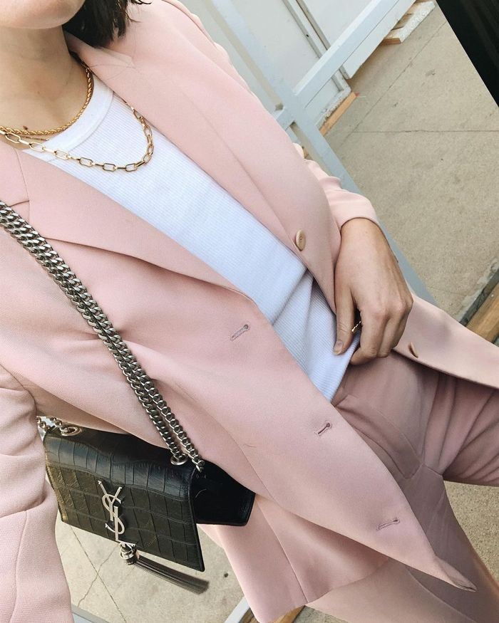 Woman wearing pink suit, white T-shirt and gold jewelry with black YSL bag