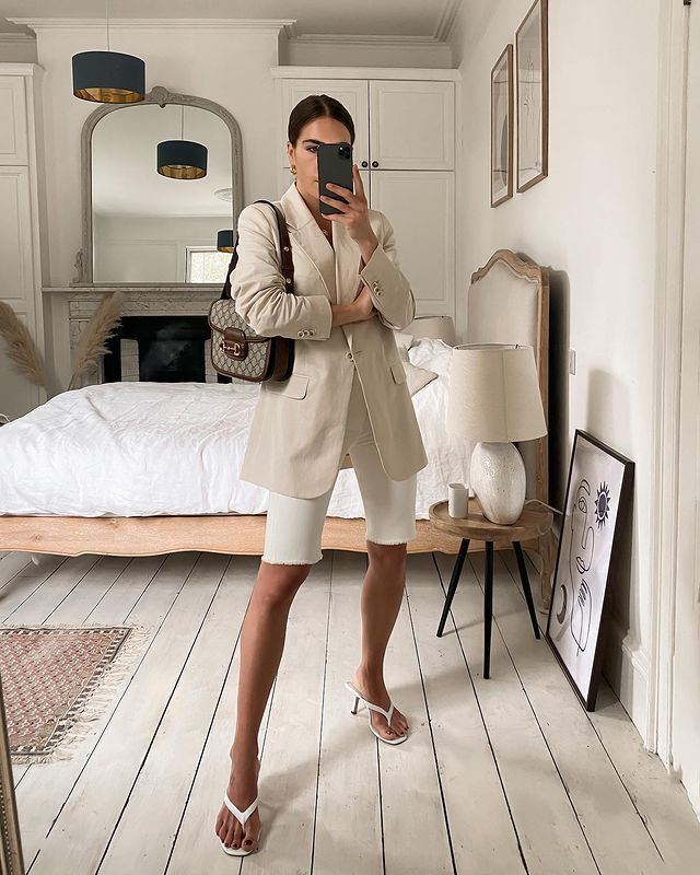 Biker Shorts Outfits: @_jessicaskye wears a pair of white bike shorts with a beige blazer and heels