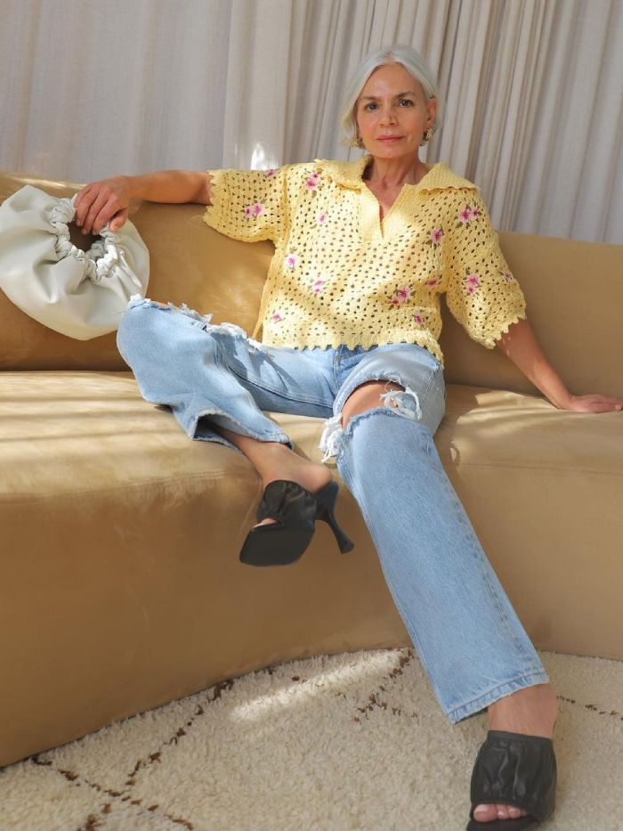 ripped jeans trend: grece ghanem wearing ripped jeans with a crochet top and black mules