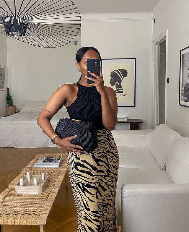 Animal Print Skirts: @femmeblk wears a knitted tiger skirt with a black racer vest