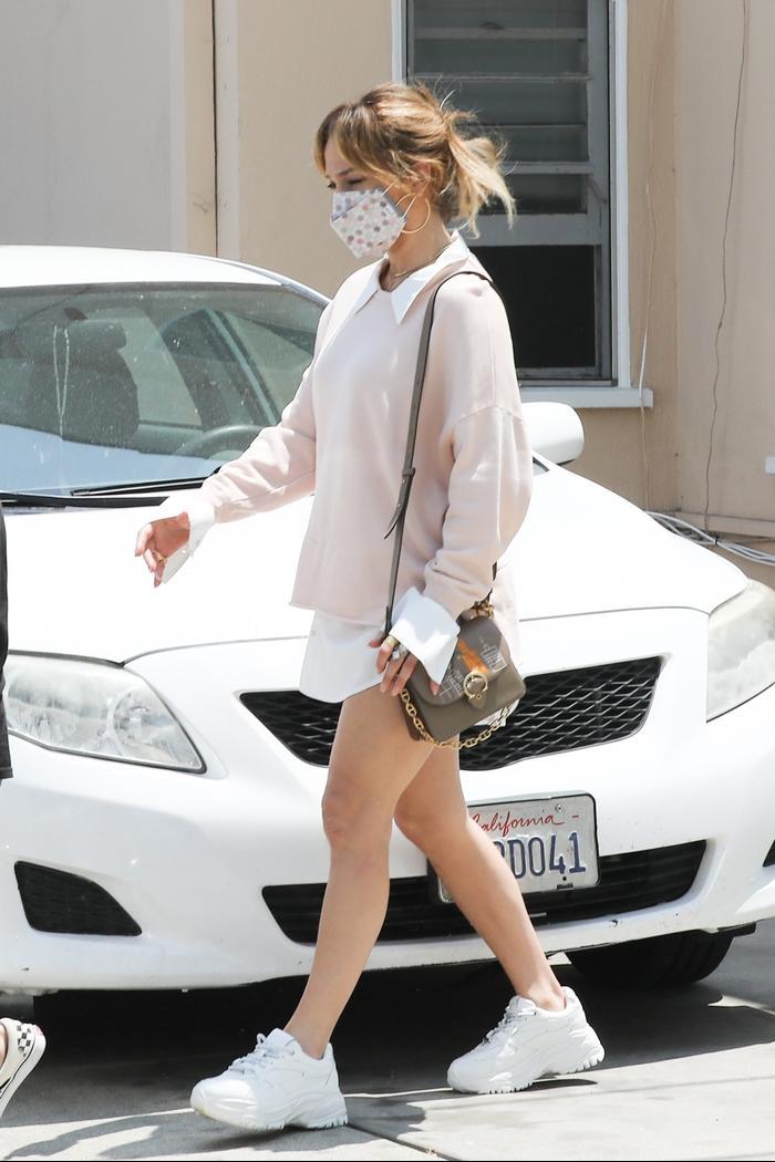 Jennifer Lopez wearing platform sneakers and a button-down shirt