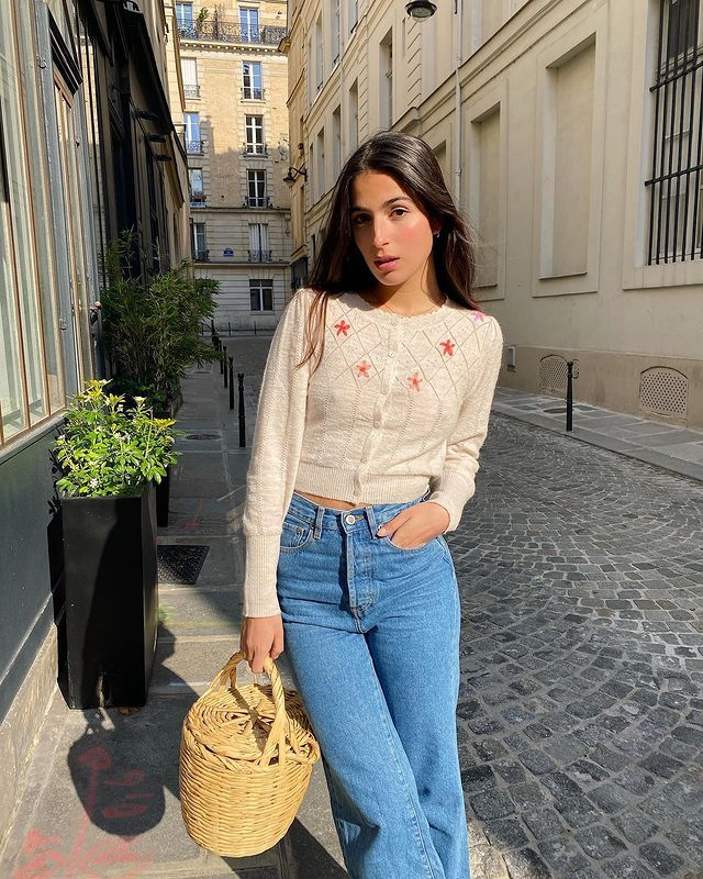 French Capsule Wardrobe: @tamaramory wears an embroidered cardigan, jeans, and carries a basket bag