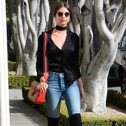 Emily Ratajkowski wears skinny jeans and over-the-knee boots.