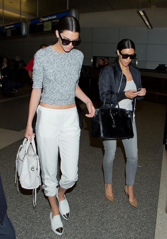Kendall Jenner in Topshop sweater and pants, Miu Miu sneakers, Balenciaga bag