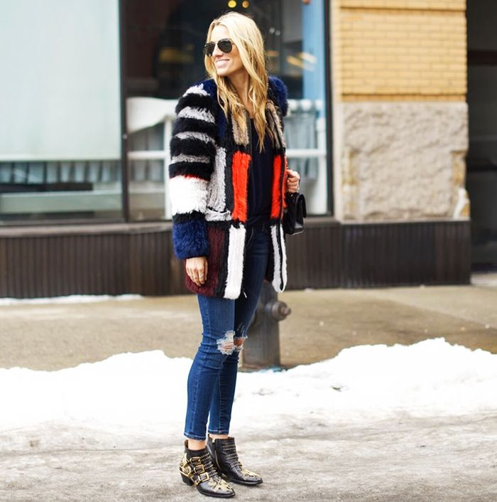A fur coat with ripped jeans and ankle boots