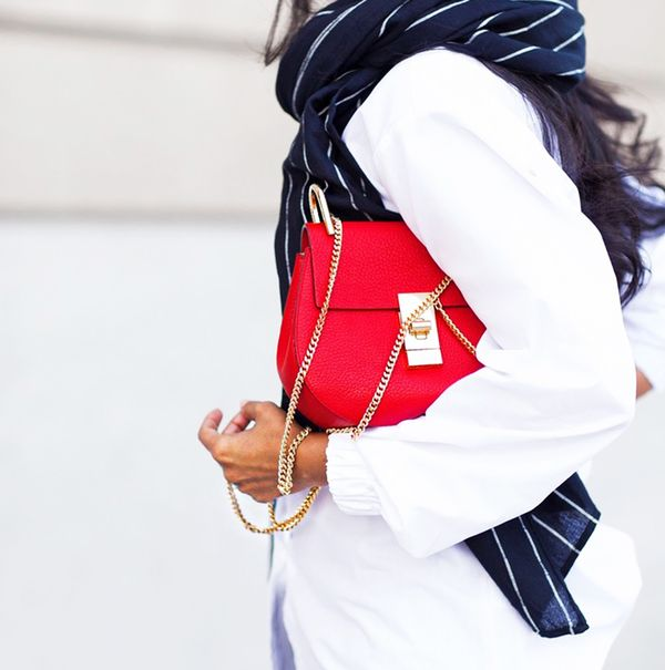 White blouse with striped navy scarf and bright red purse