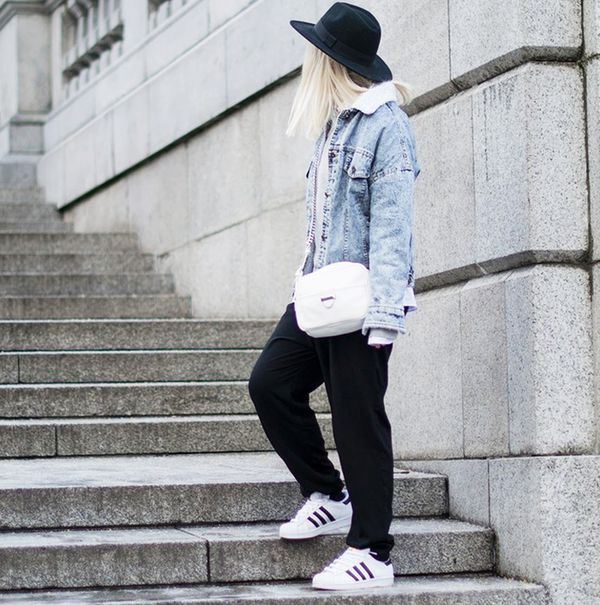 Denim jacket with sweatpants, Adidas superstar sneakers, and black felt hat