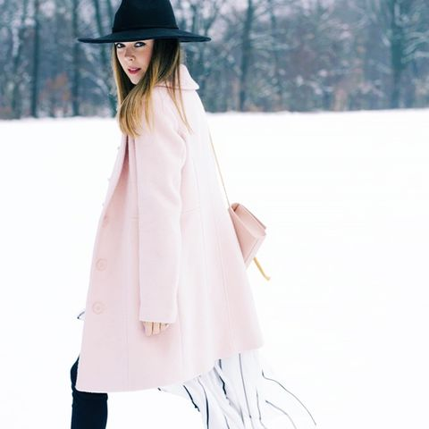Pink coat with dip hem striped blouse, black pants, pink shoulder purse and black hat