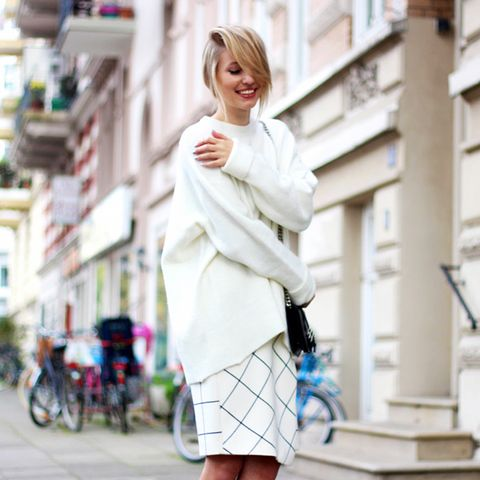 Oversized cream sweater with check midi skirt and black shoulder purse