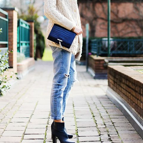 Beige cable-knit sweater, distressed jeans, ankle boots, and shoulder purse