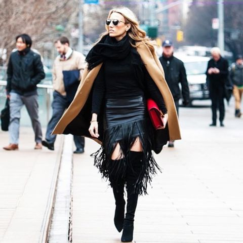 Black sweater with black fringe mini skirt, over-the-knee boots and camel coat