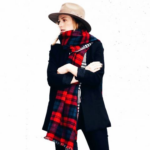 Red plaid scarf with black coat, black pants, and tan hat