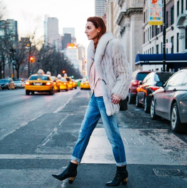 White fur coat, pink blouse, girlfriend jeans, and black ankle boots
