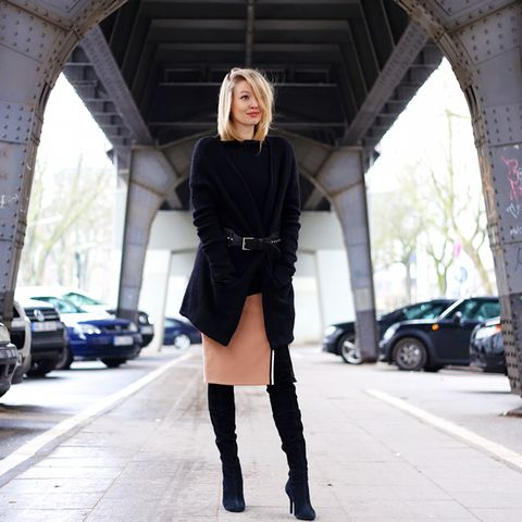 Oversized black sweater with belt, black over the knee boots, and beige midi skirt with slit